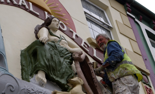 Photo of Freddie Chute working on the restoration of the Maid of Erin, Listowel, a project managed by Ciarán Walsh of  www.cutrator.ie for artist Sean Lynch. Lynch was commissioned by Kerry County Council as part of its Public Art Funding. The photo is split, one half showing the 'Maid' stripped bare and the second half showing the 'Maid' after restoration.